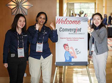Women posed around sign for women connect doing an arm muscle pose