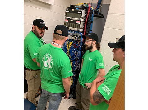 Men in server room dealing with cables and wiring