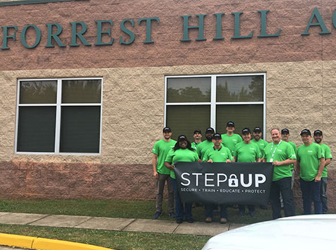Convergint APS team posing outside of school with banner