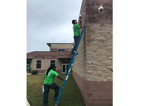 Men installing security camera on side of school one standing on ladder