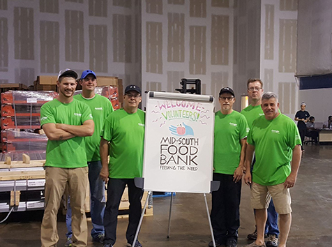 People posing with food bank sign