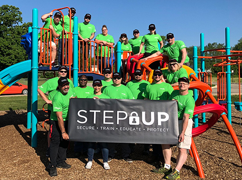 People posing on playground with a STEP Up banner
