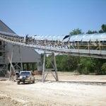 Crews installing conveyor cover on large belt system with crane