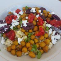 Pečena čičerika s feto, olivami in rdečo papriko na kuhani proseni kaši