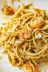 shrimp pesto spaghetti on a white plate up close.