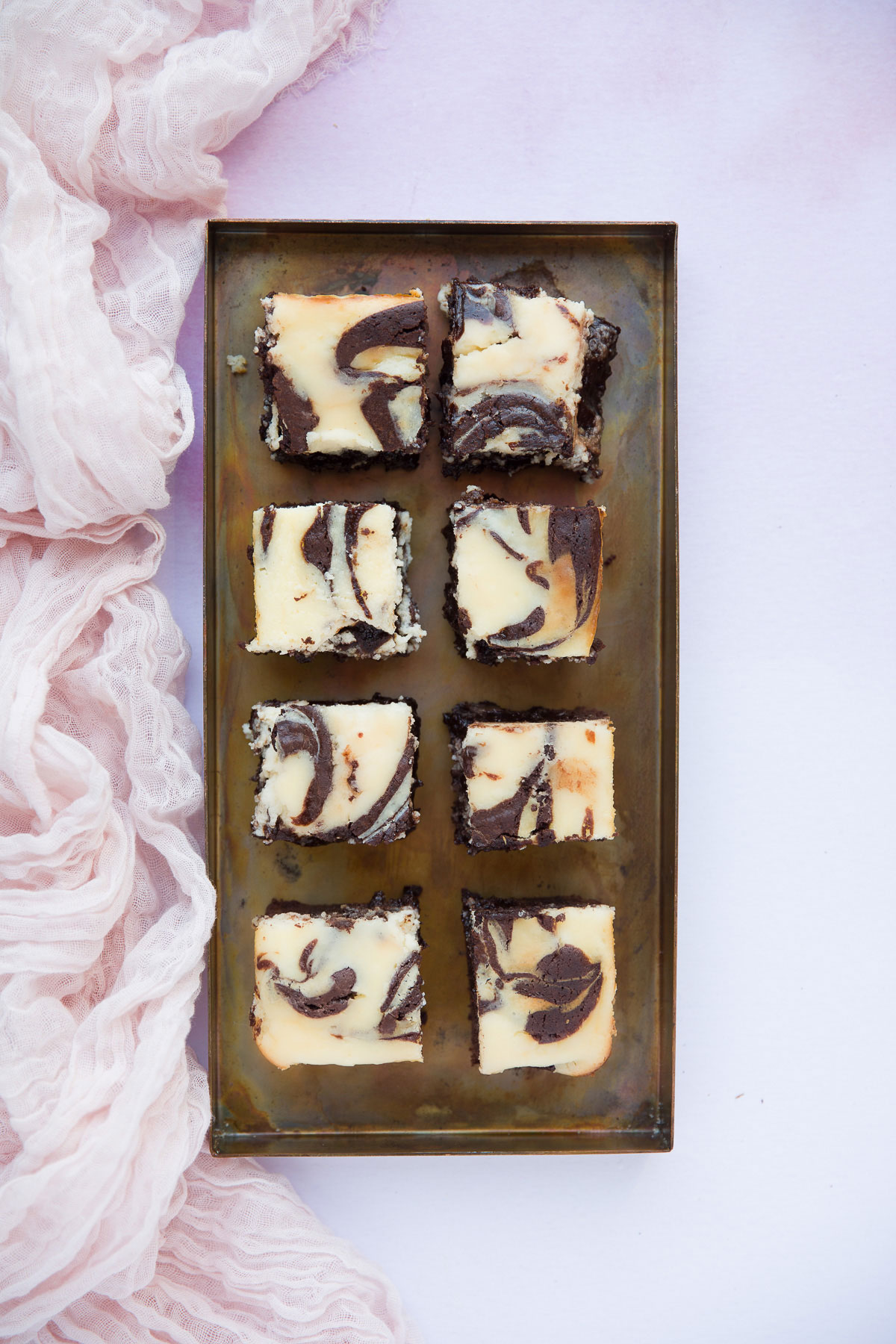 eight brownies on a serving dish with a pink towel on the side.