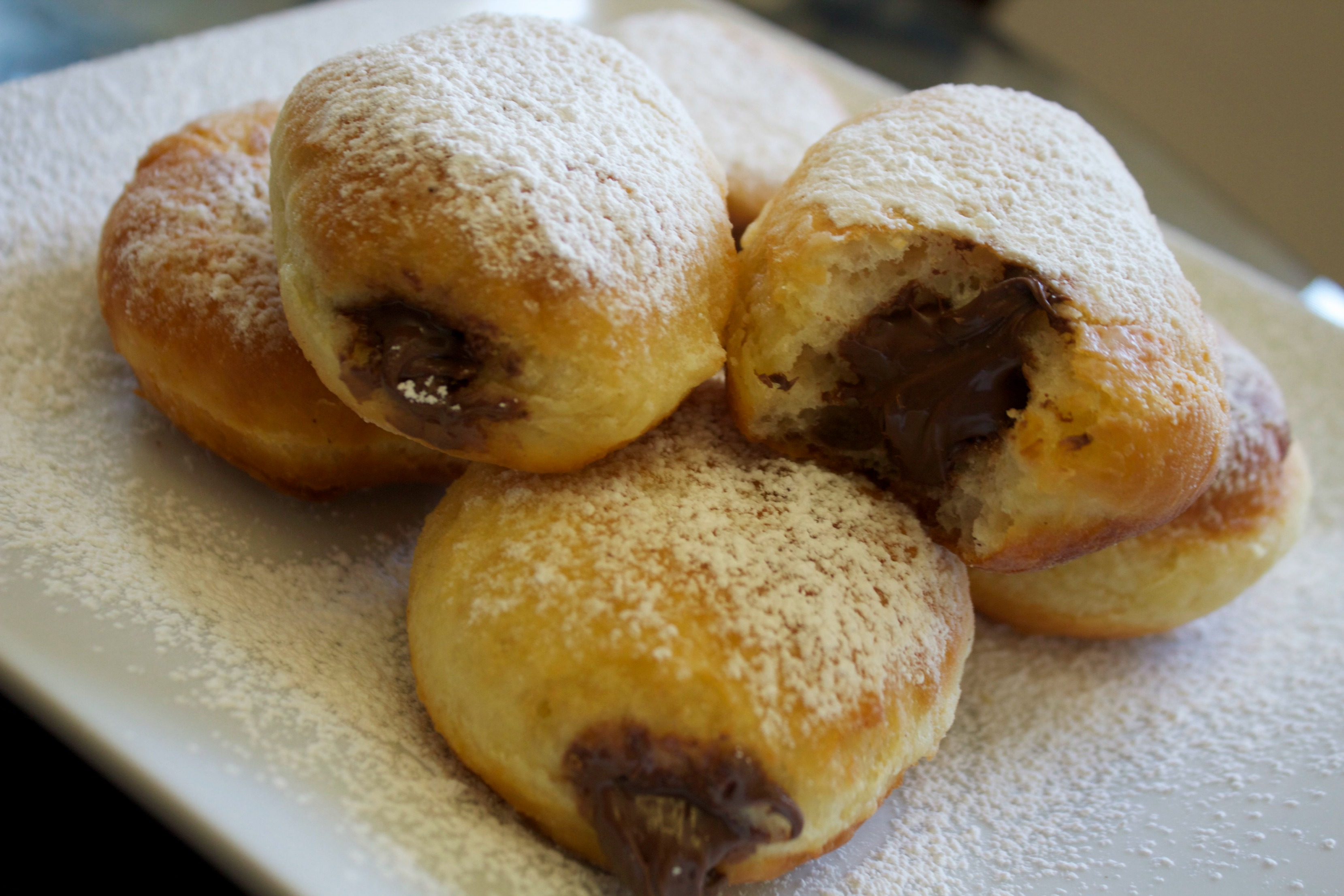 Nutella Stuffed Donuts made with a chocolate hazelnut spread filling and dusted with powdered sugar.