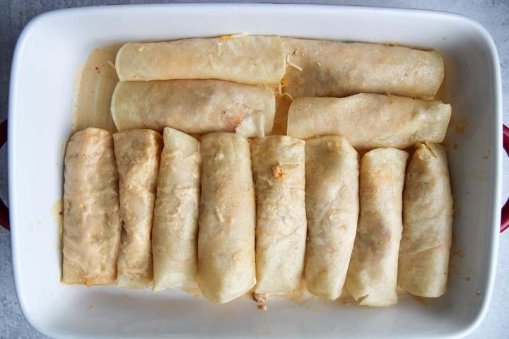 twelve rolled corn tortillas in a white casserole dish.