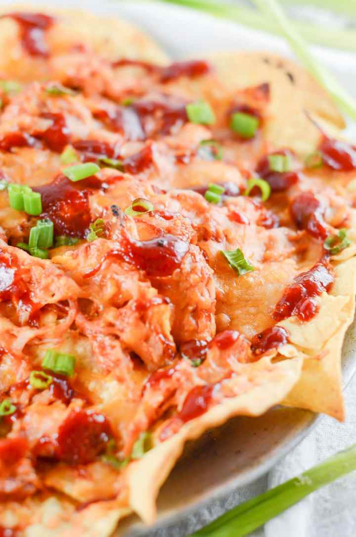 nachos with pulled chicken, bbq sauce, cheese, and scallions on a plate.