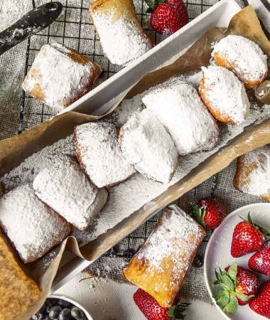 a long bog with brown paper and beignets inside. beignets on the side of the box along with strawberries and blueberries.