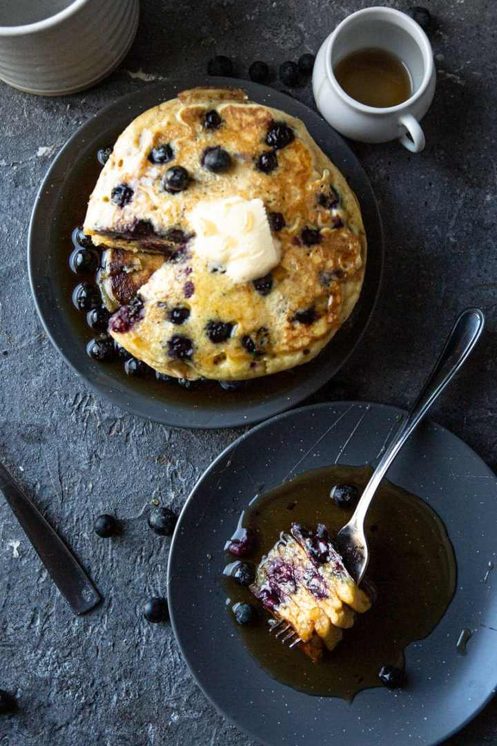 a short stack of blueberry pancakes and a small plate with a fork and four pancake slices.