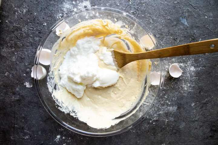 A bowl with pancake batter and folded egg whites with a spatula. Egg shells on the side of the bowl.