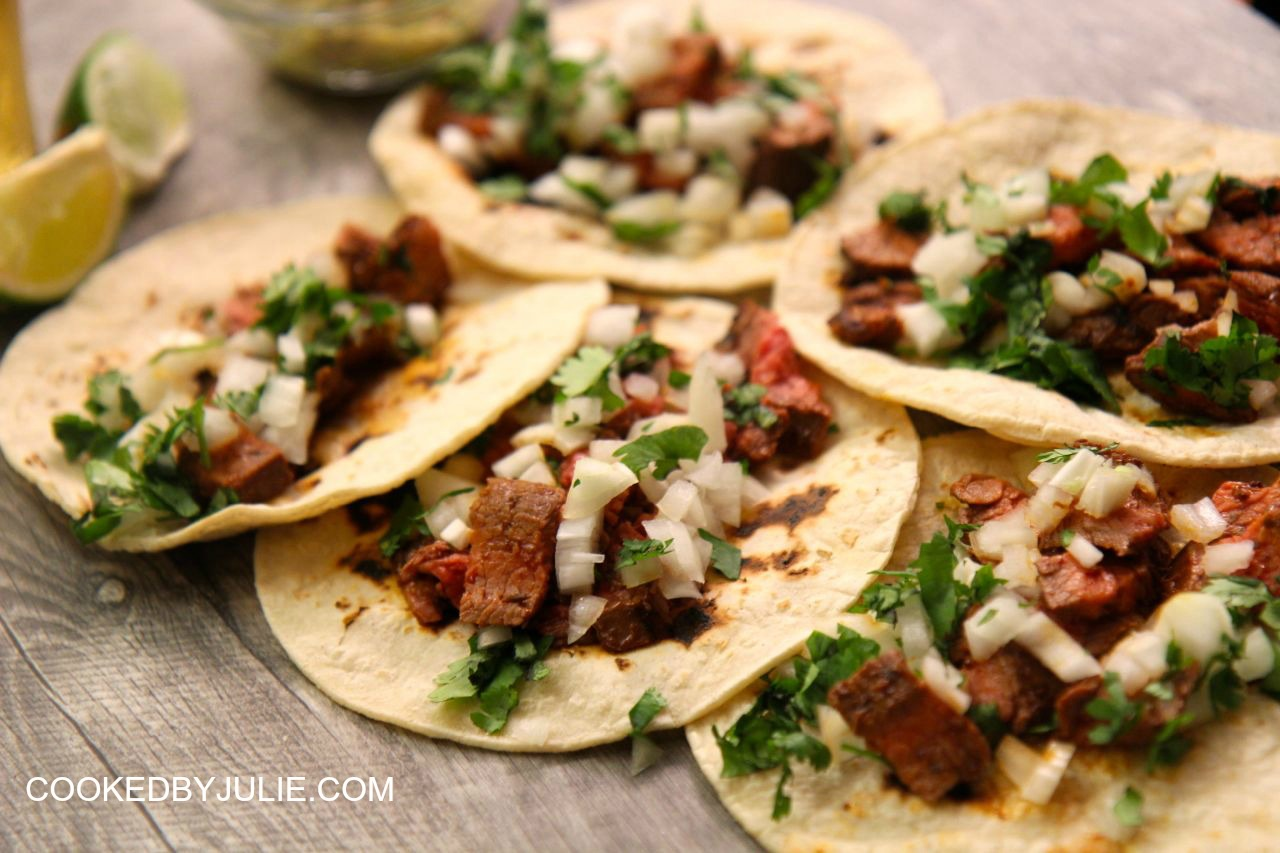 Carne asada tacos served on corn tortillas with onions and cilantro