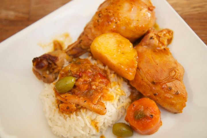 fricase de pollo over white rice on a white plate.