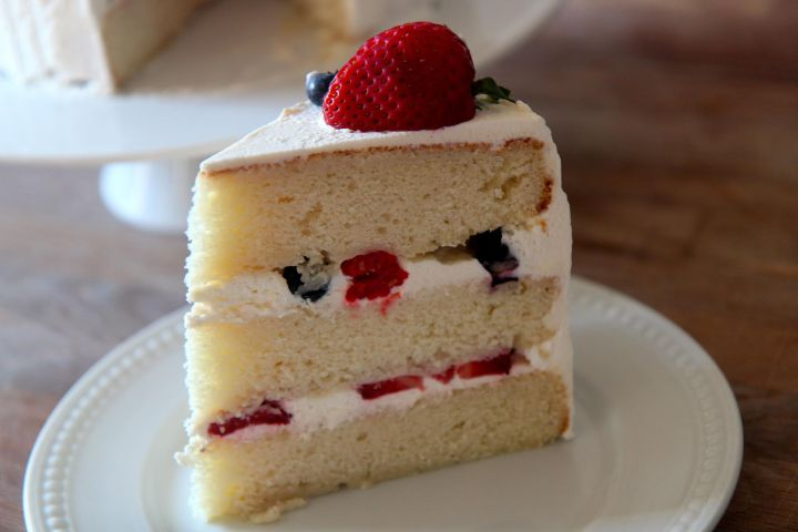 Three layers of yellow cake with a sweet vanilla frosting and filled with raspberries, strawberries, and blueberries