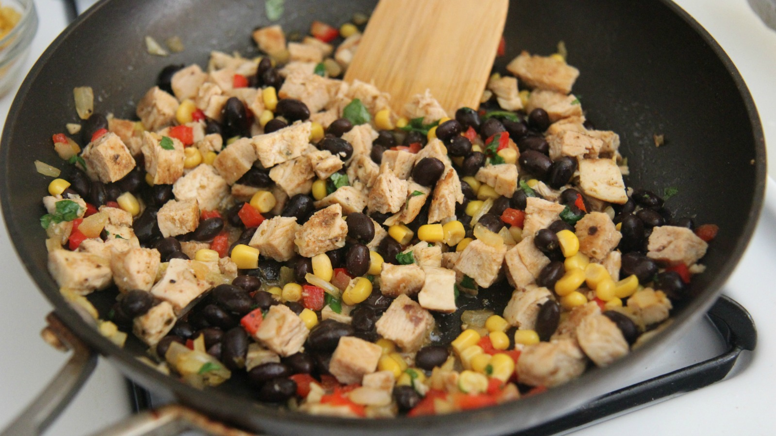 Mix the cubed chicken in with the beans, corn, pepper and more spices. Don't overcook or the chicken will become dry.