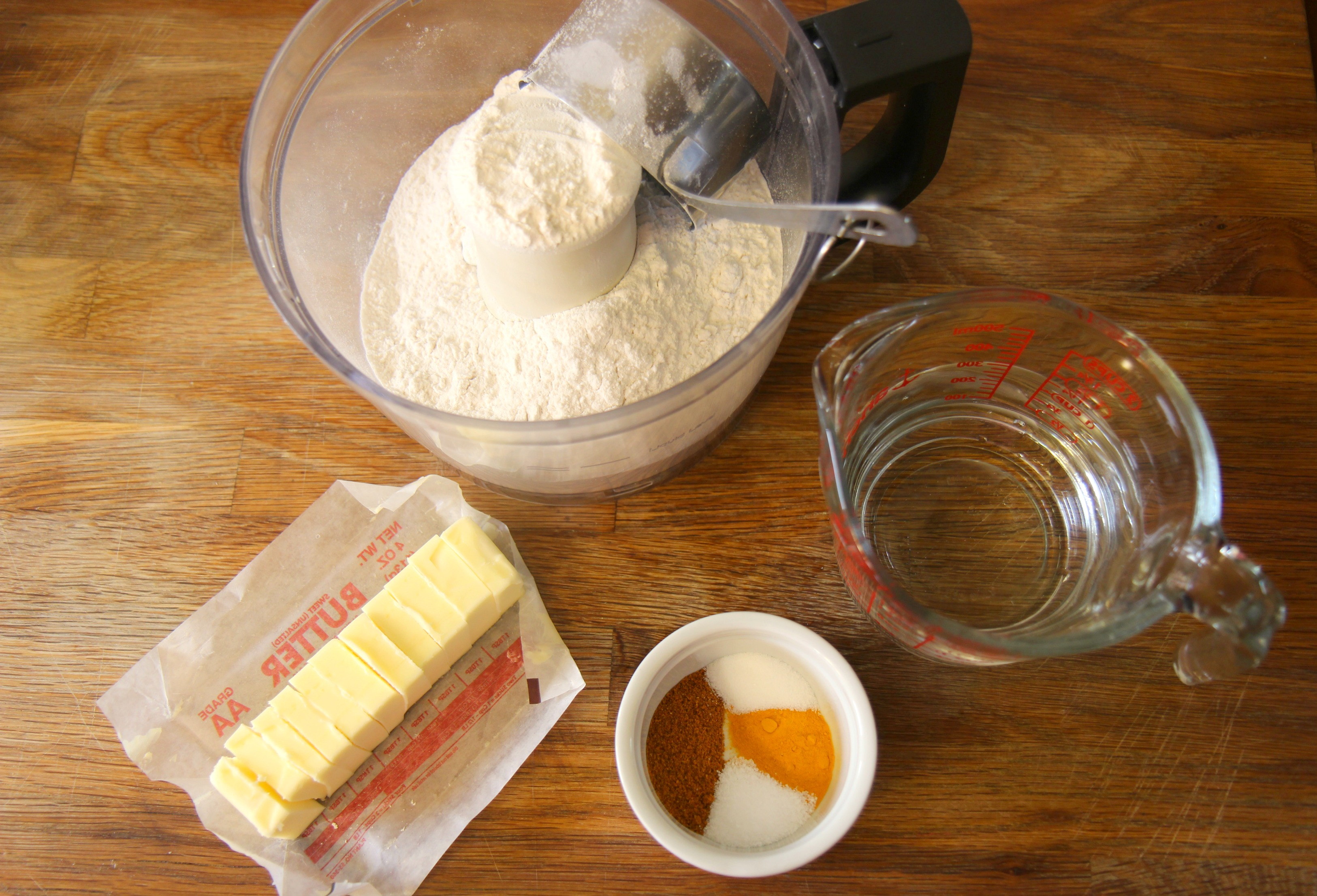 flour in a food processor, stick of butter, spices in a small ramekin, and a measuring cup with water.