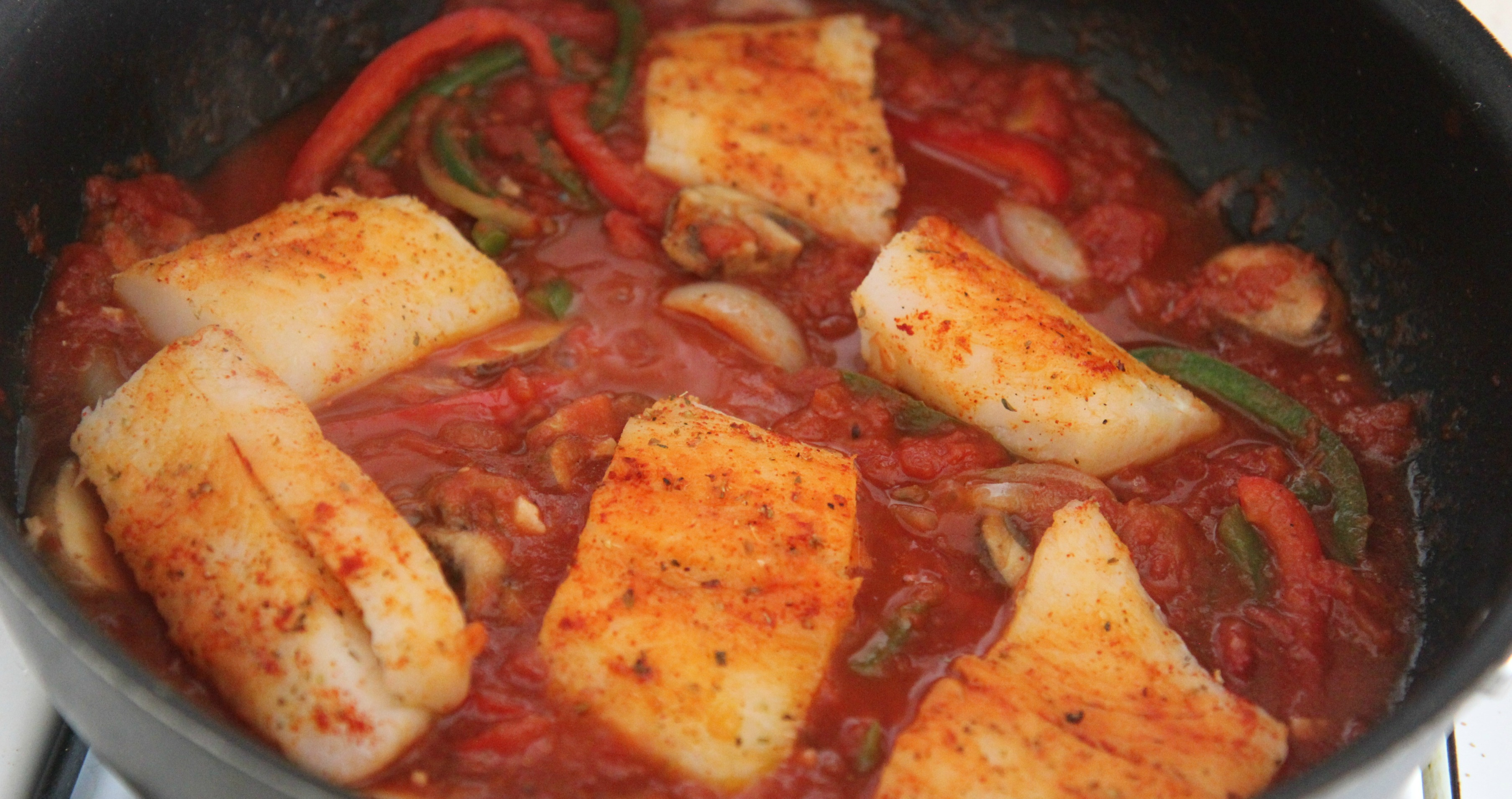Cook the seasoned cod fish with your tomato sauce and vegetables for 12-15 minutes until fully cooked.