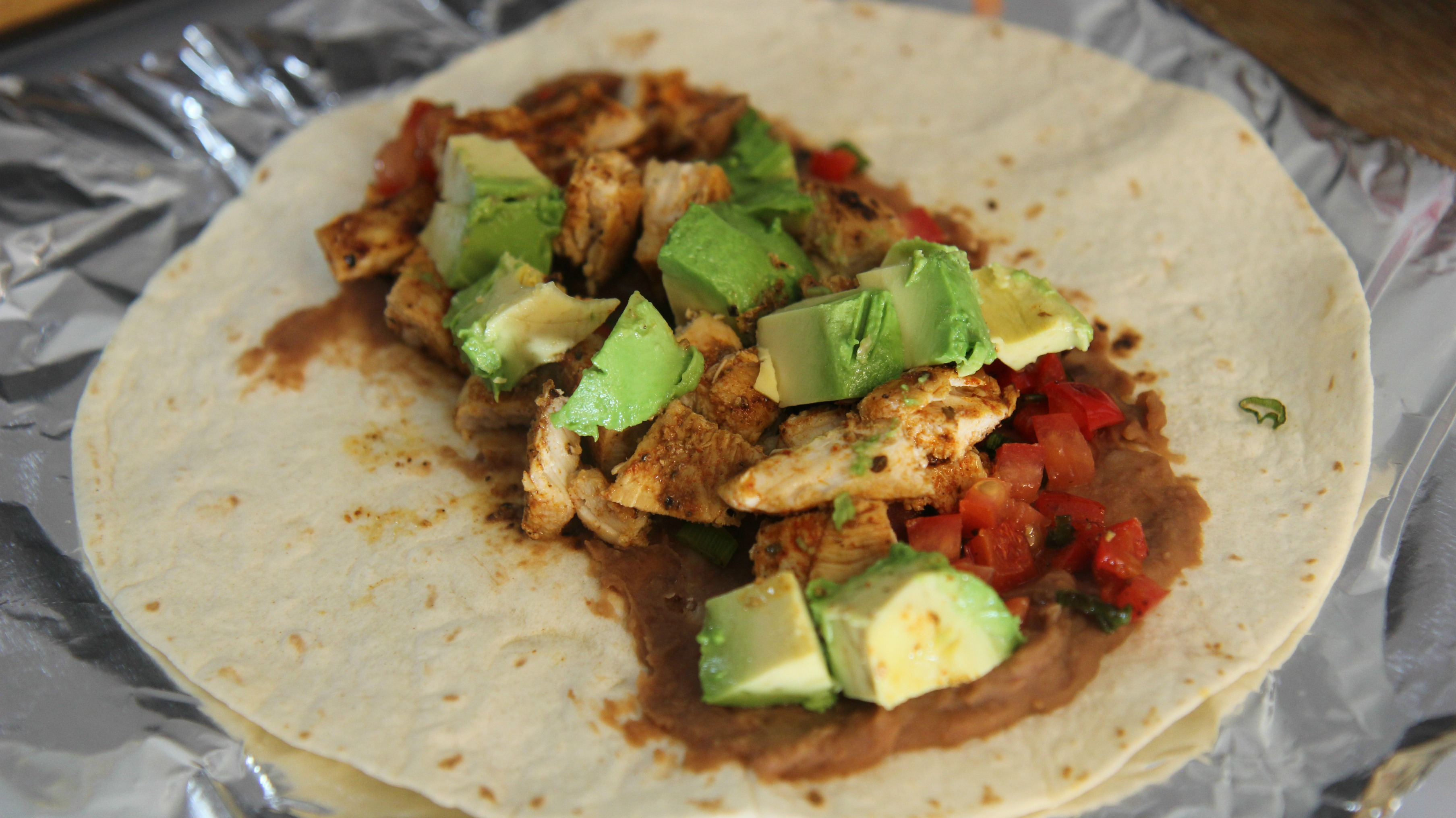 Add the chicken to a tortilla with refried beans, avocado chunks and some tomatoes.