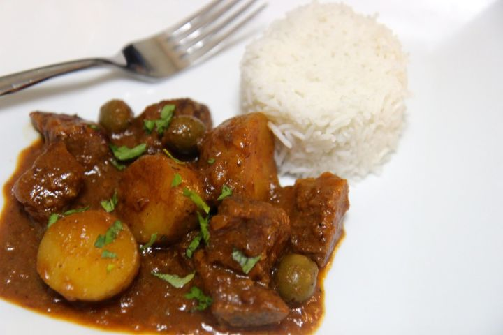 carne con papa with white rice and a fork on a white plate