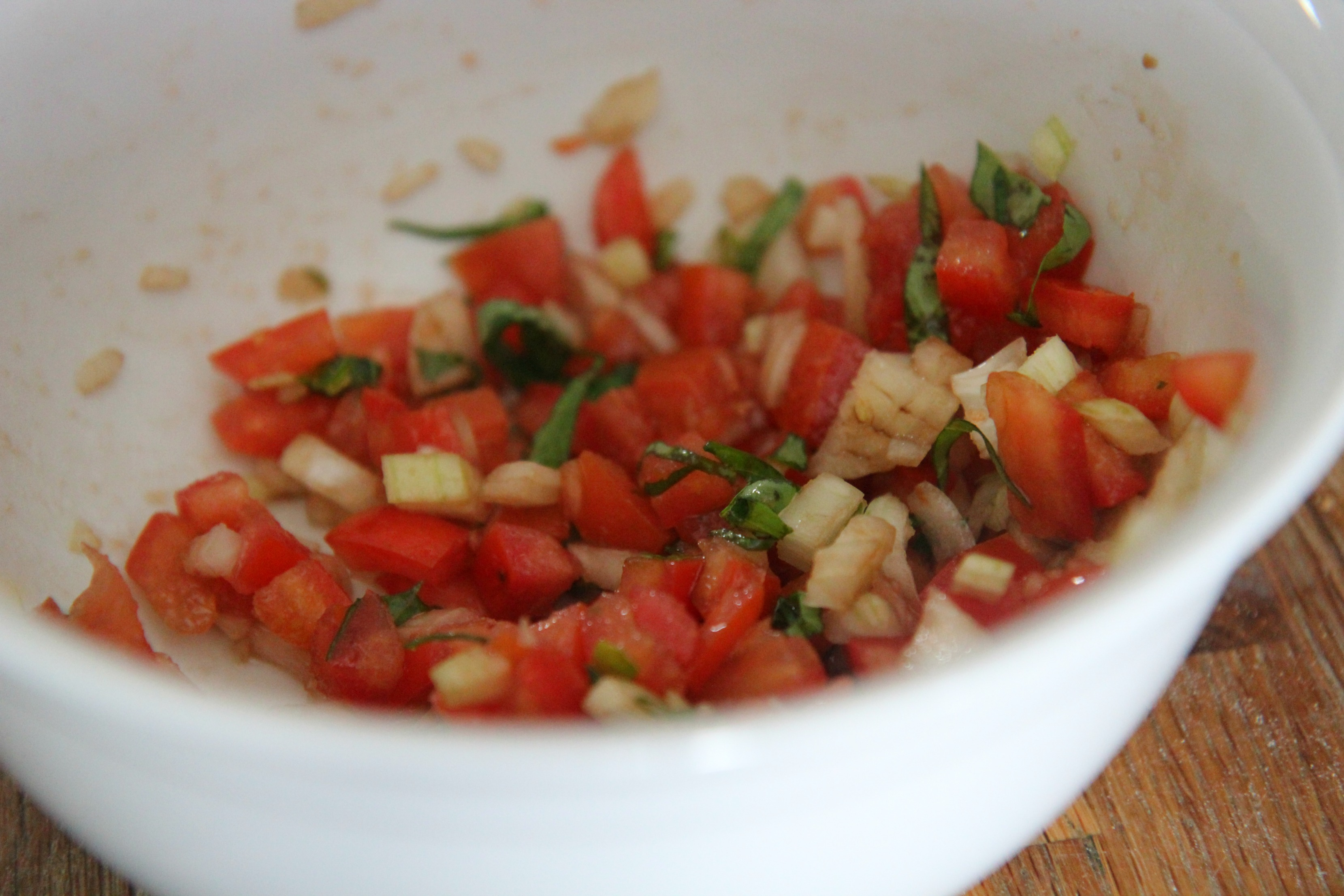 Tomatoes, onions, and basil mixed with a drizzle of balsamic dressing.