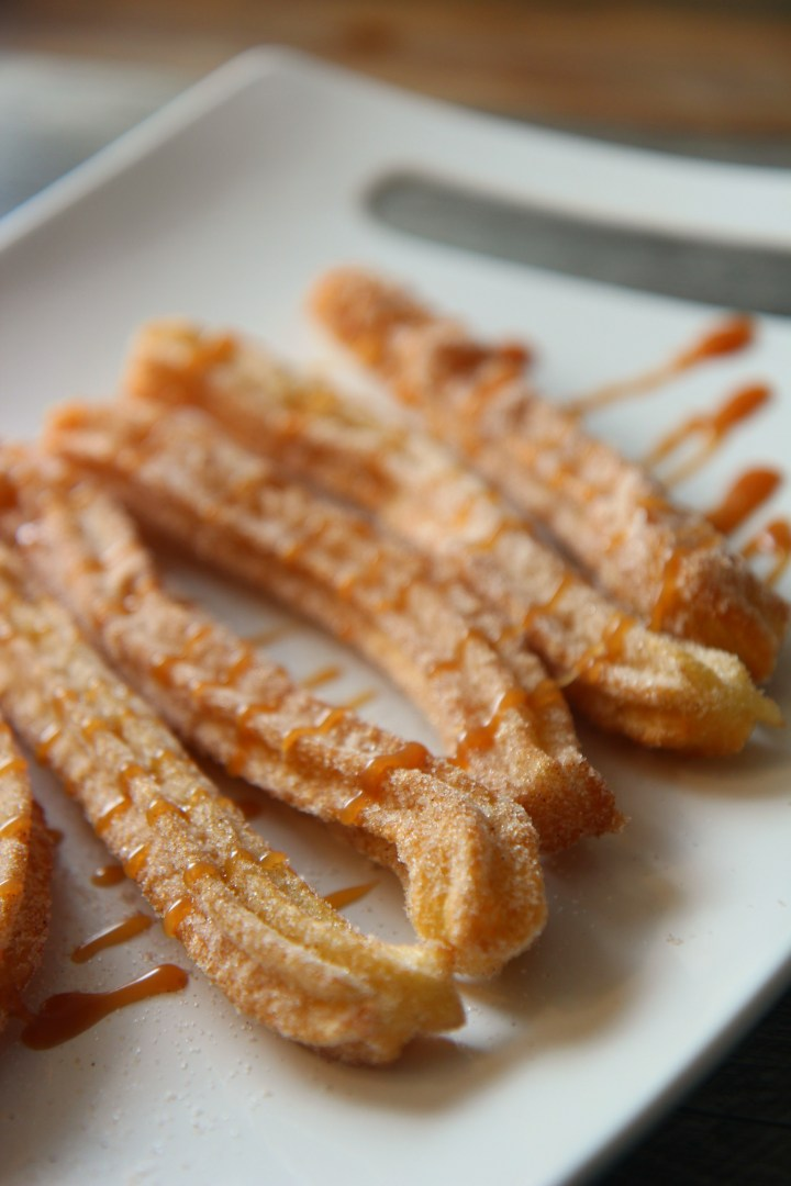 five churros on a white plate.