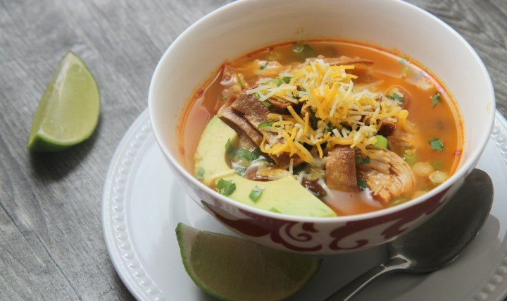 Spicy chicken tortilla soup topped with cheddar cheese and avocado