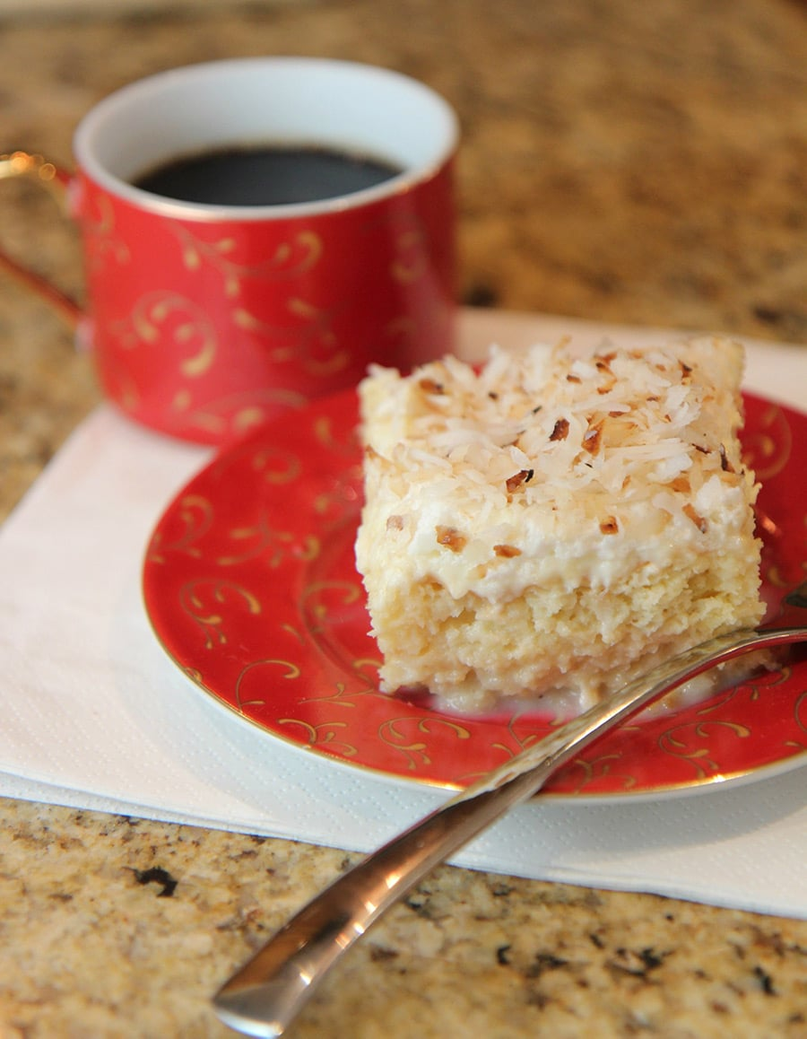 a slice of tres leches coconut cake on a red small plate with a cup of coffee on the side and a fork.
