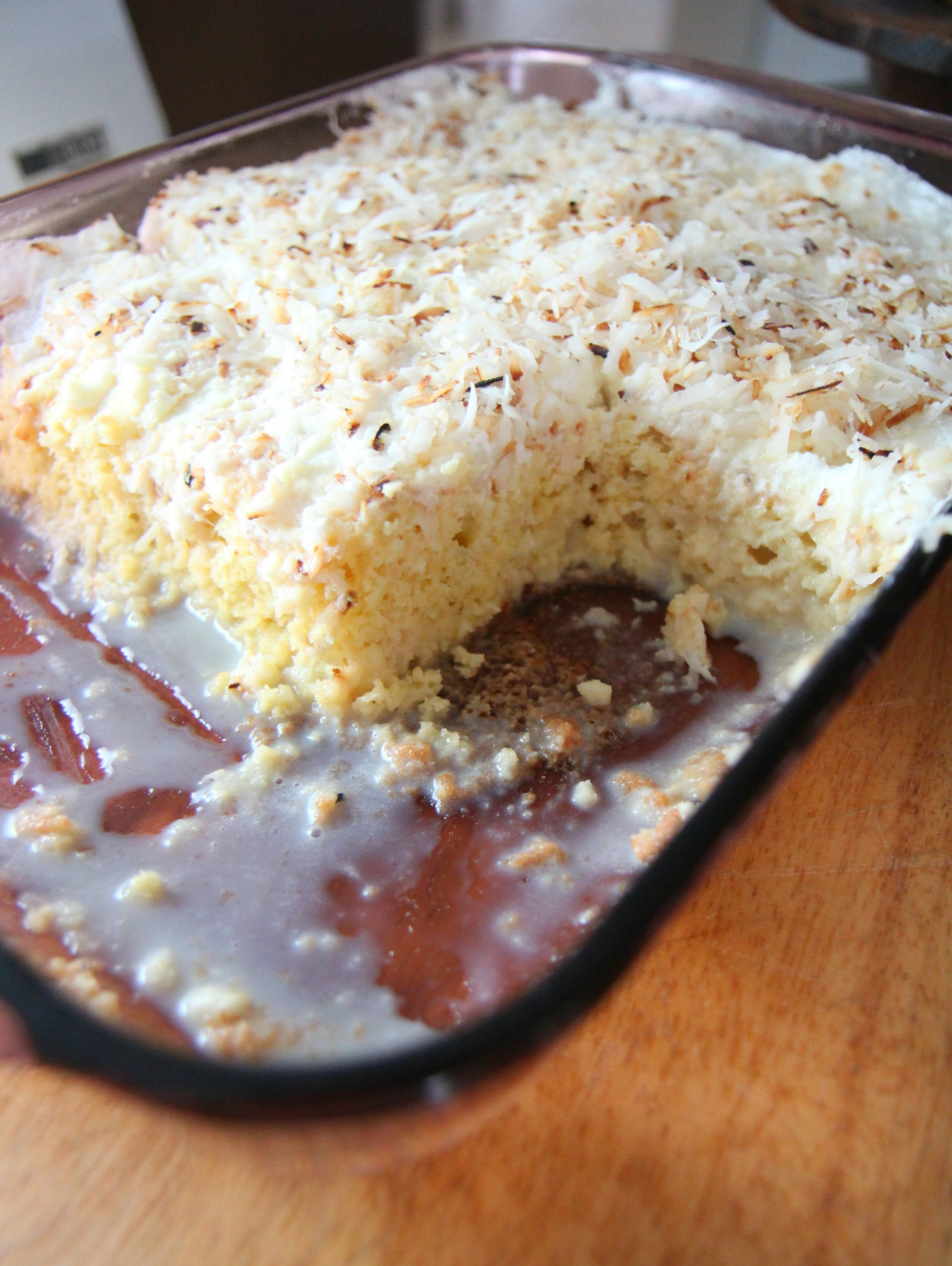 Moist tres leches cake topped with frosting and toasted coconut.