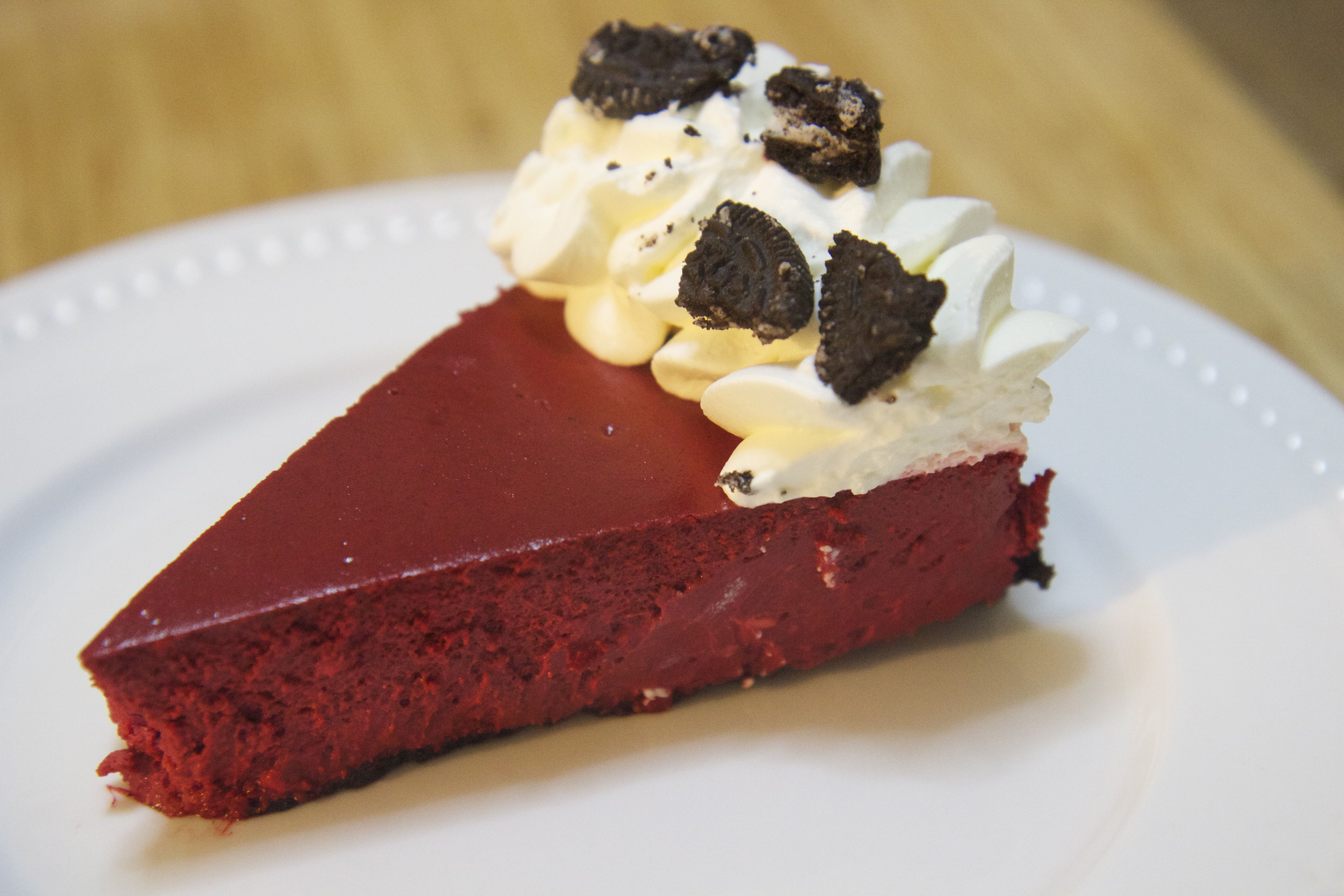 Red velvet cheesecake with an Oreo cookie crust and cream cheese frosting.