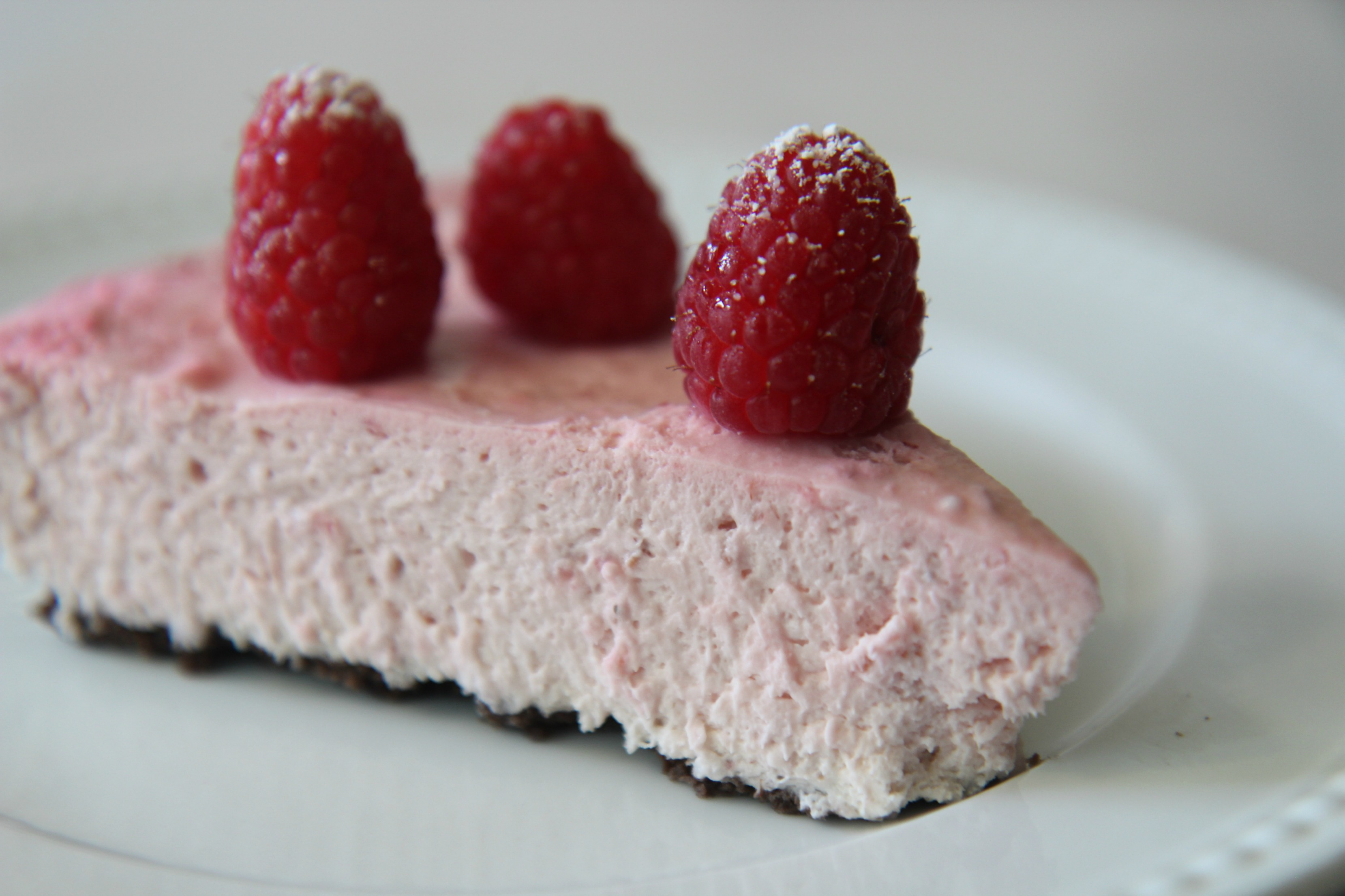 A light and fluffy slice of a no-bake white chocolate raspberry tart with a chocolate cookie crust topped with fresh raspberries and powdered sugar