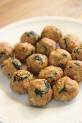 fifteen spinach and turkey meatballs on a white plate.