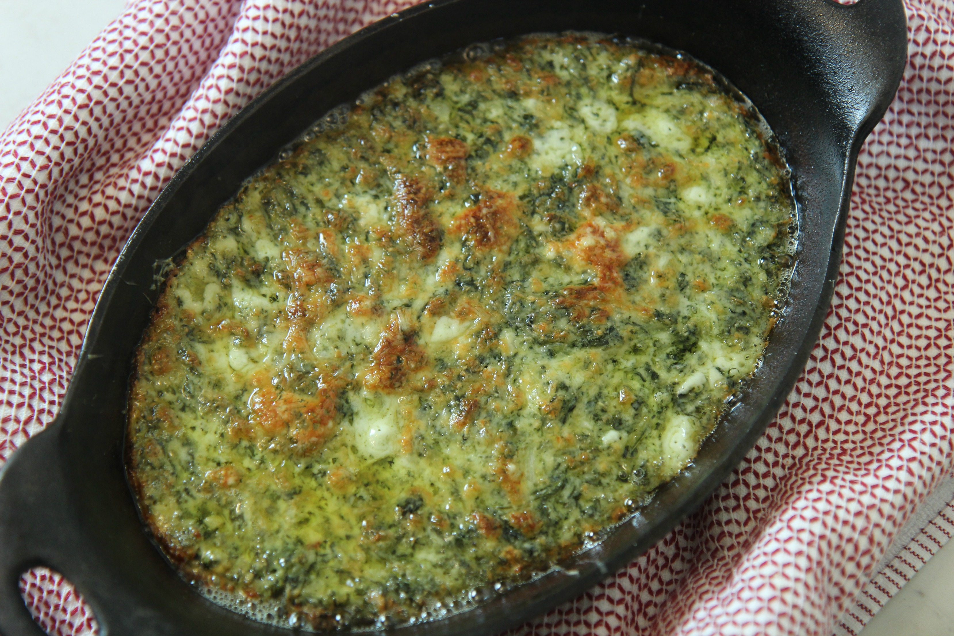 This spinach dip has a delicious cheesy baked crust that's perfect for dipping.