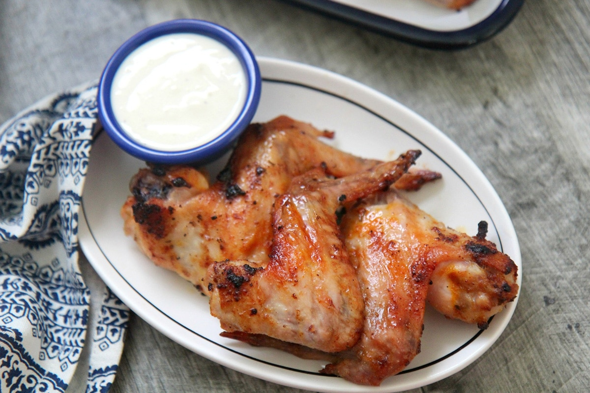 three wings on a white plate with a small side of dipping sauce and a blue and white towel on the side.