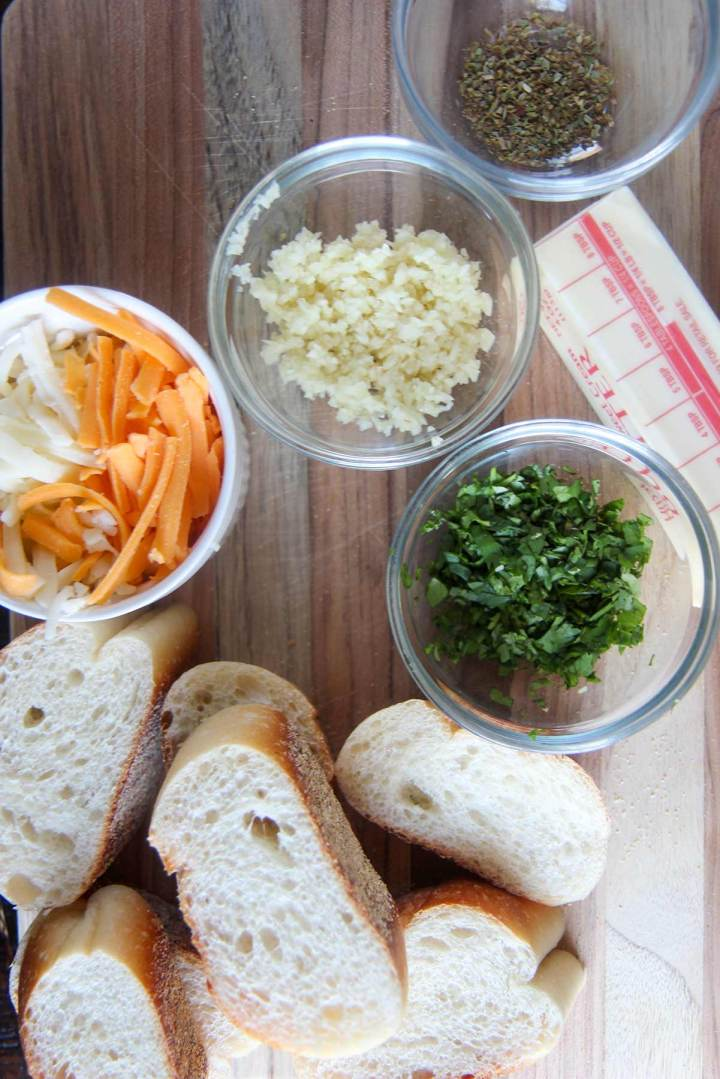 cheese, garlic, and herbs in small bowls and bread and butter on a wooden board.
