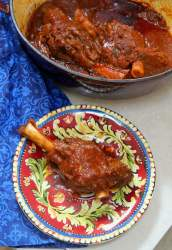braised lamb shank of a red and yellow plate with a red pot in the background with lamb and a blue towel on the side.