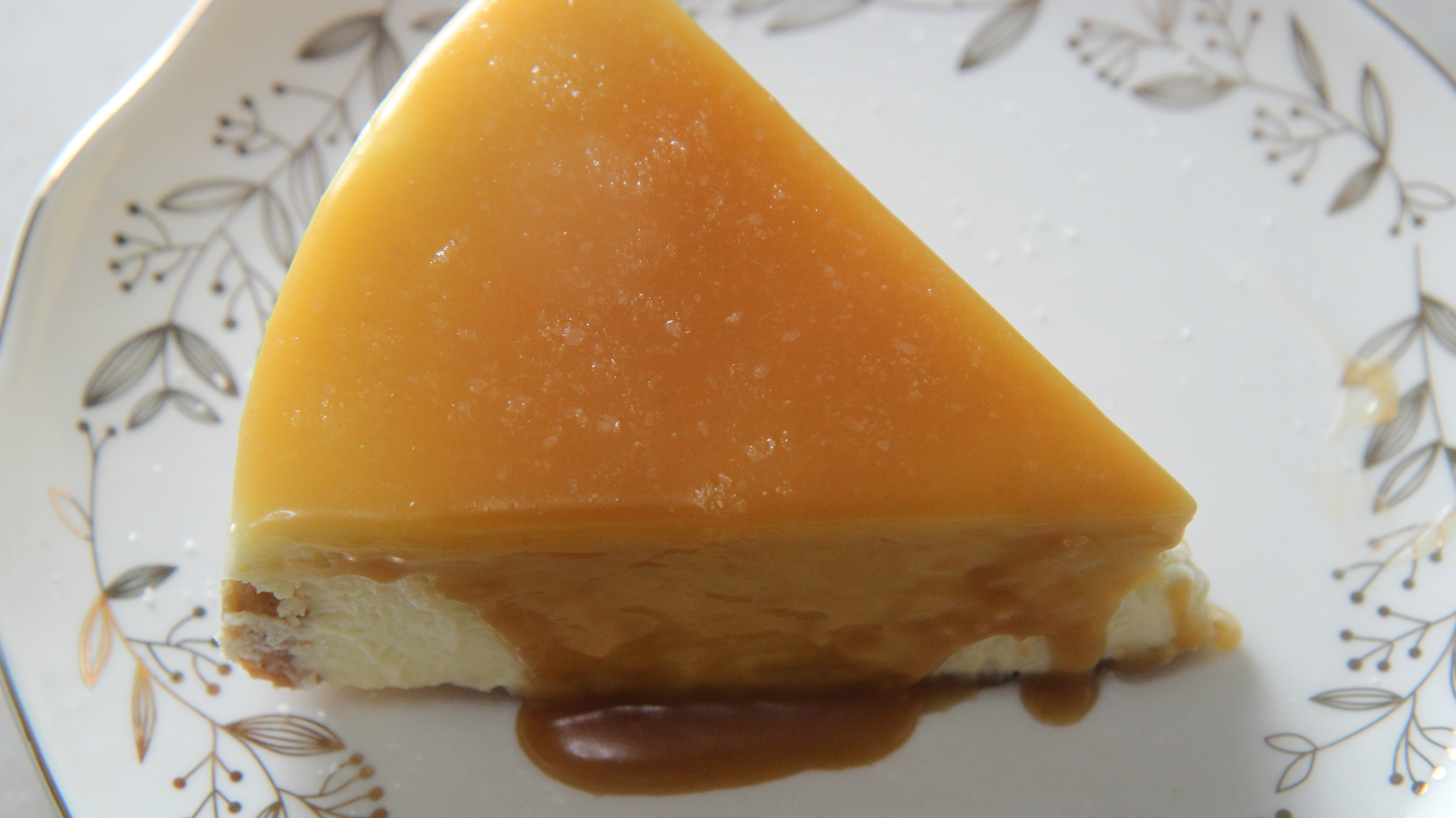 a slice of salted caramel cheesecake on a white plate