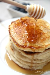 5 stacked pancakes on a plate with a honey comb over it