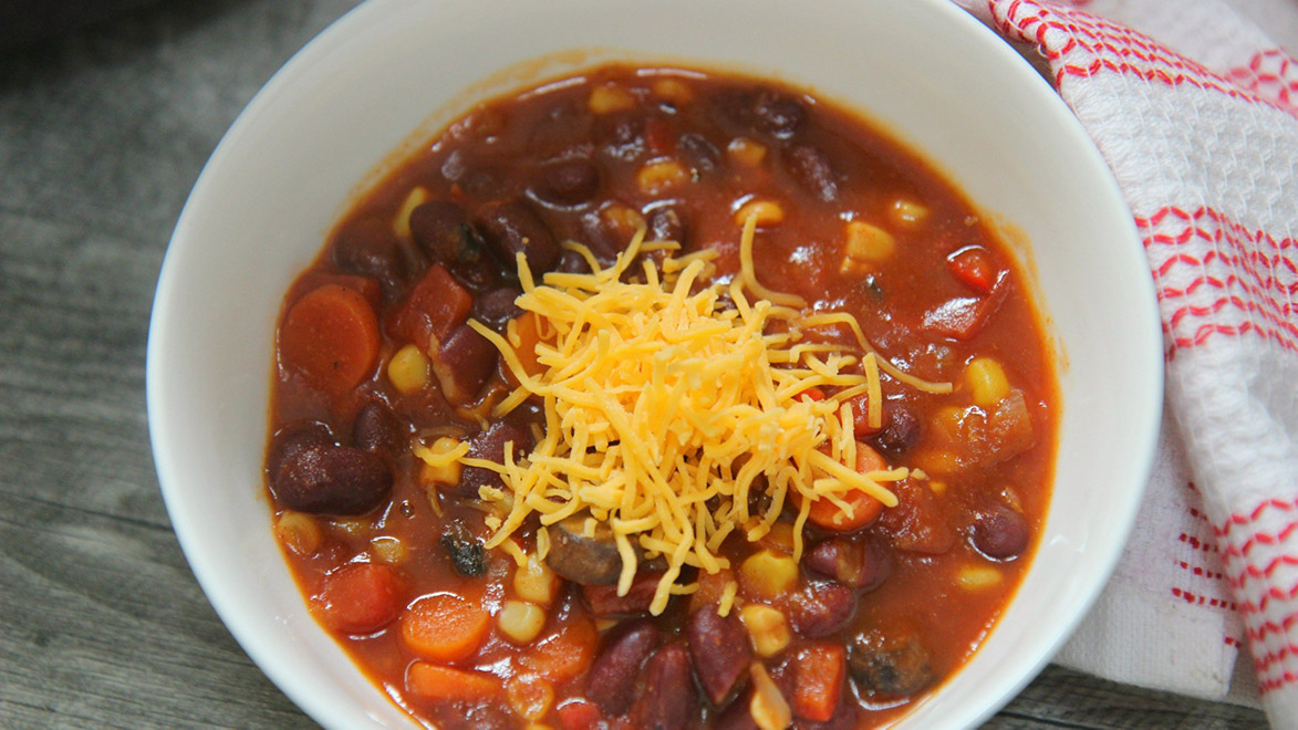 a small bowl of chili with shredded cheddar cheese on top