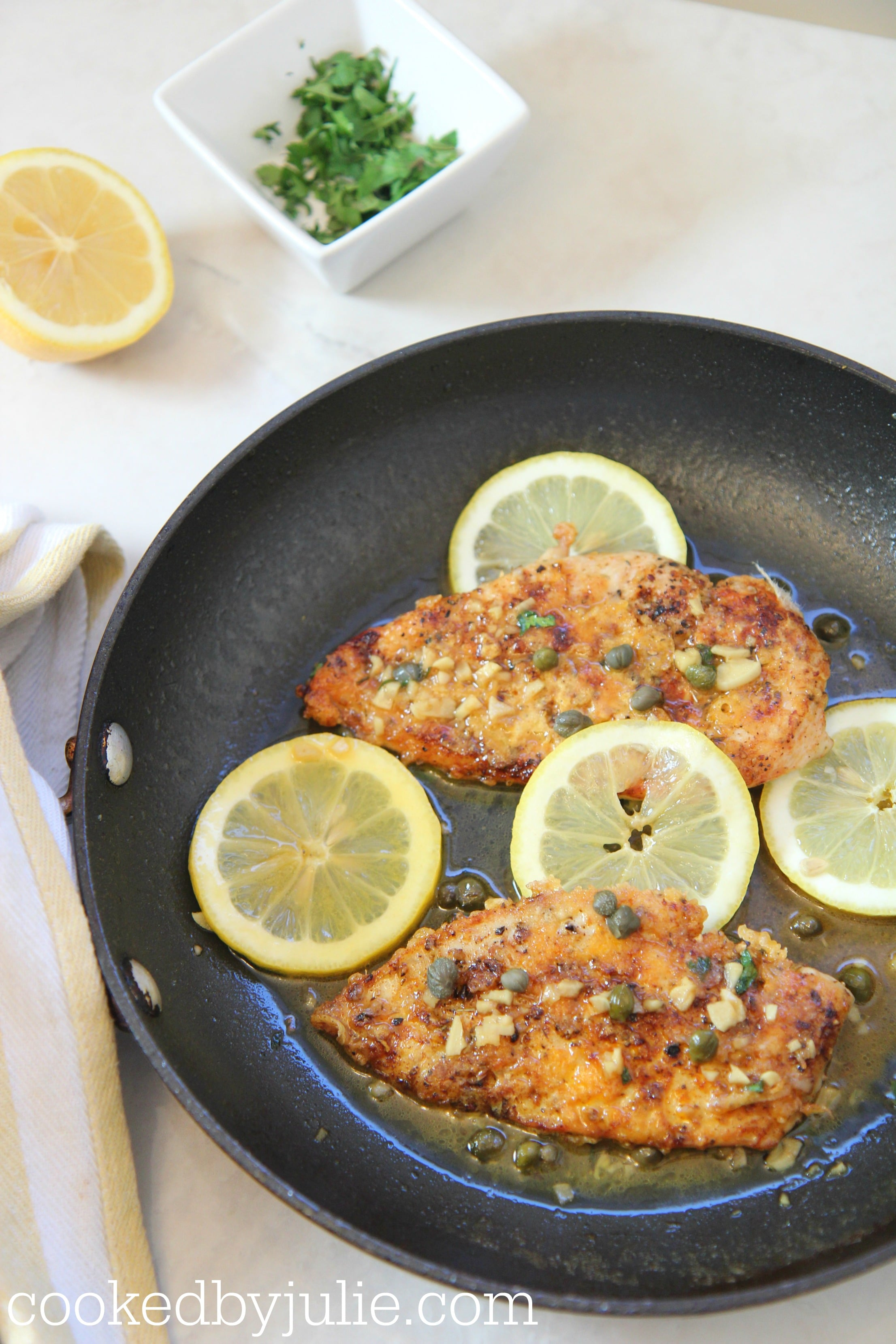 chicken piccata in a skillet with lemon and a small ramekin with parsley.