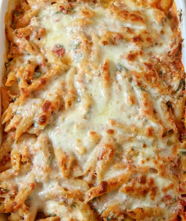 baked ziti with spinach and melted mozzarella cheese on top in a white casserole dish.