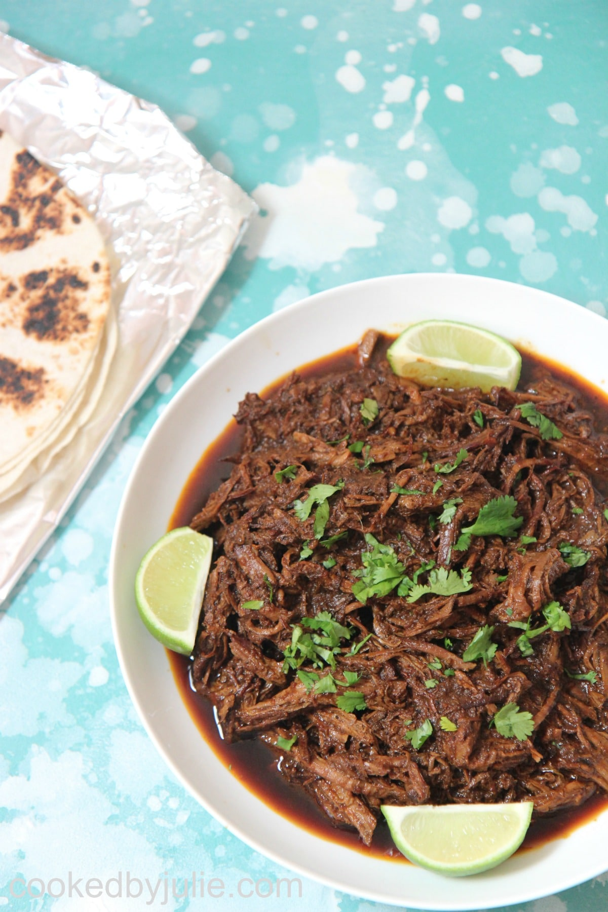 beef barbacoa with lime wedges and cilantro