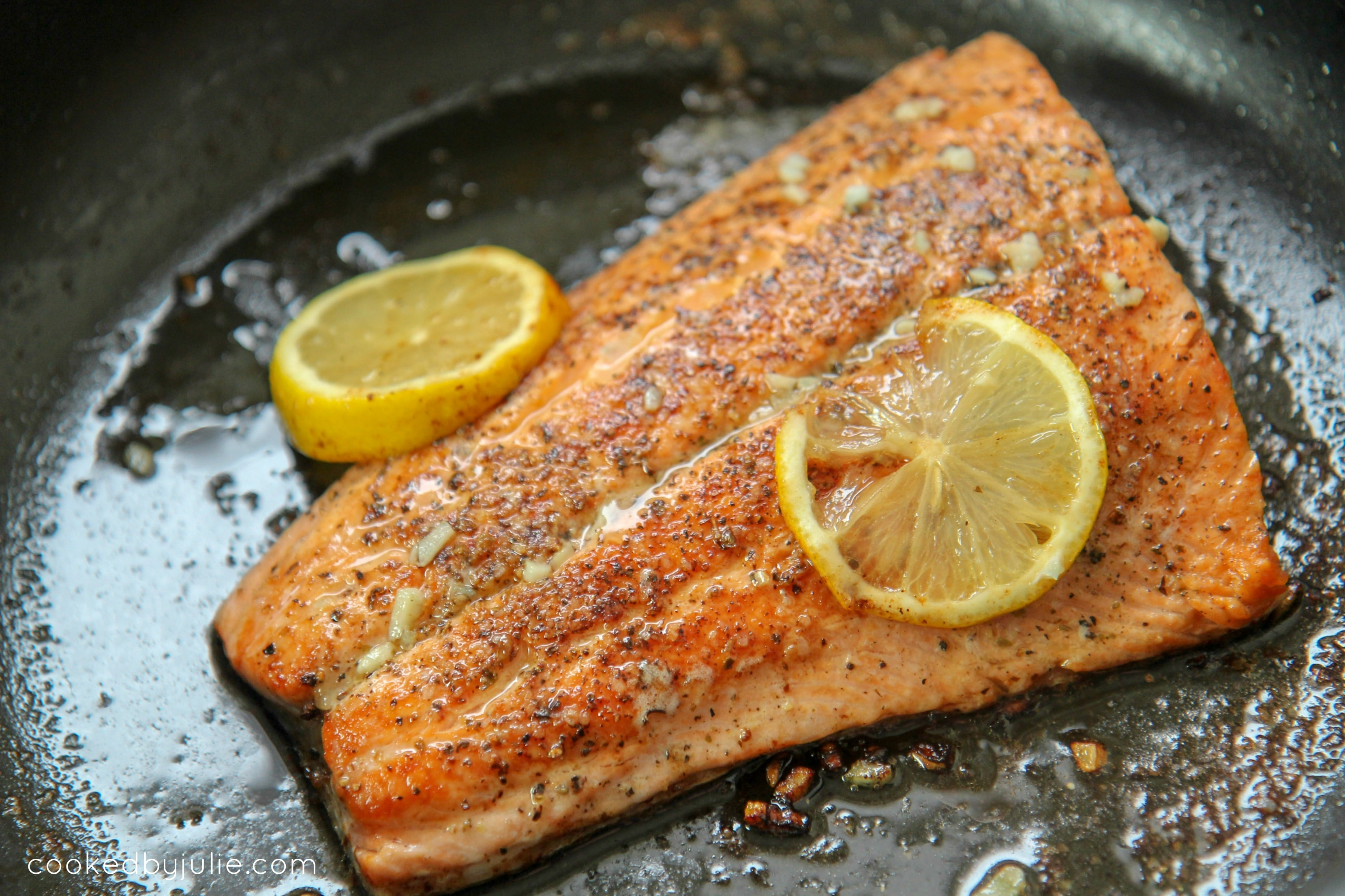 salmon filet in a large skillet with lemon slices