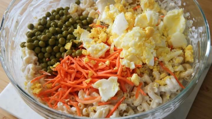 Bowl of Hawaiian Macaroni Salad Ingredients. Green peas, shredded carrots, eggs, and macaroni.