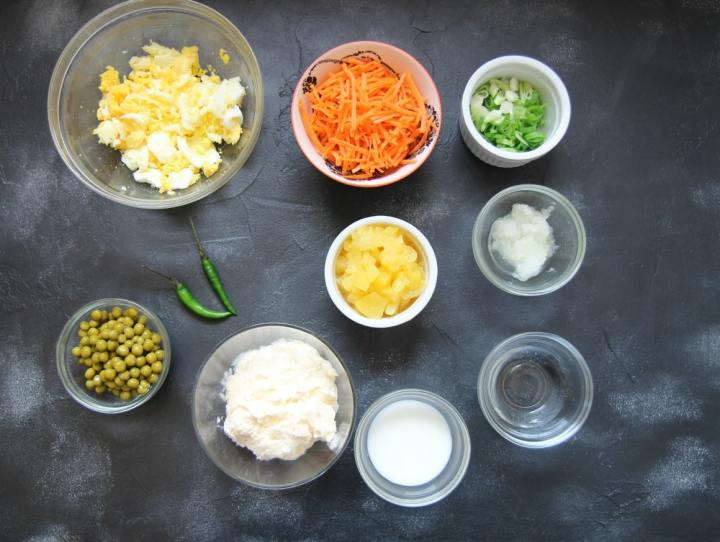 Hawaiian Macaroni Salad Ingredients. Eggs in a bowl, shredded carrots in a bowl, two green chilies, mayo in a bowl, milk, vinegar, scallions, and pineapples in separate bowls.