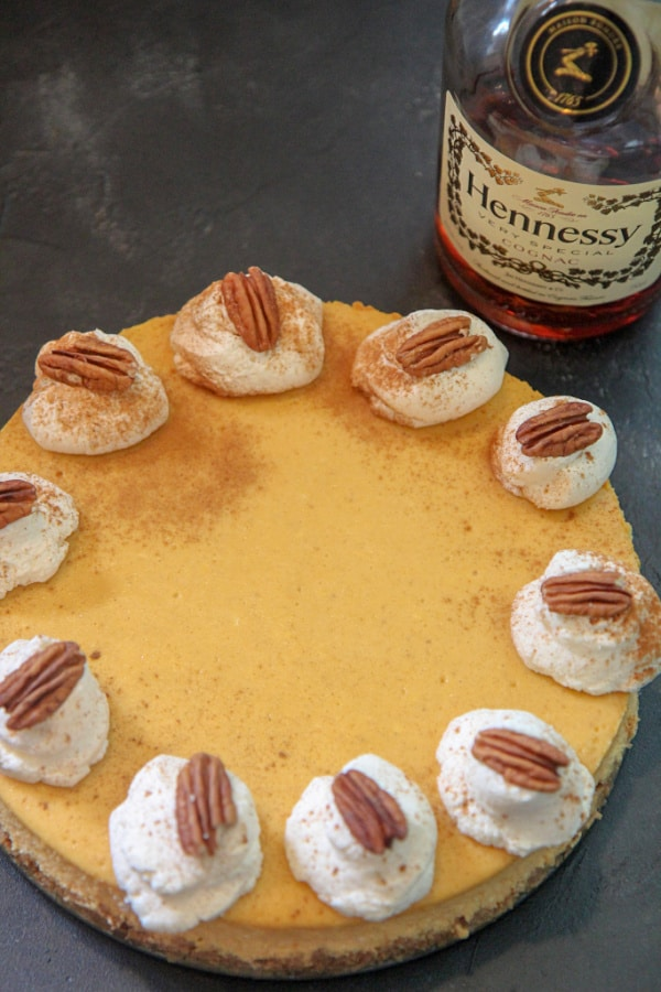 pumpkin cognac cheesecake with whipped cream and pecans