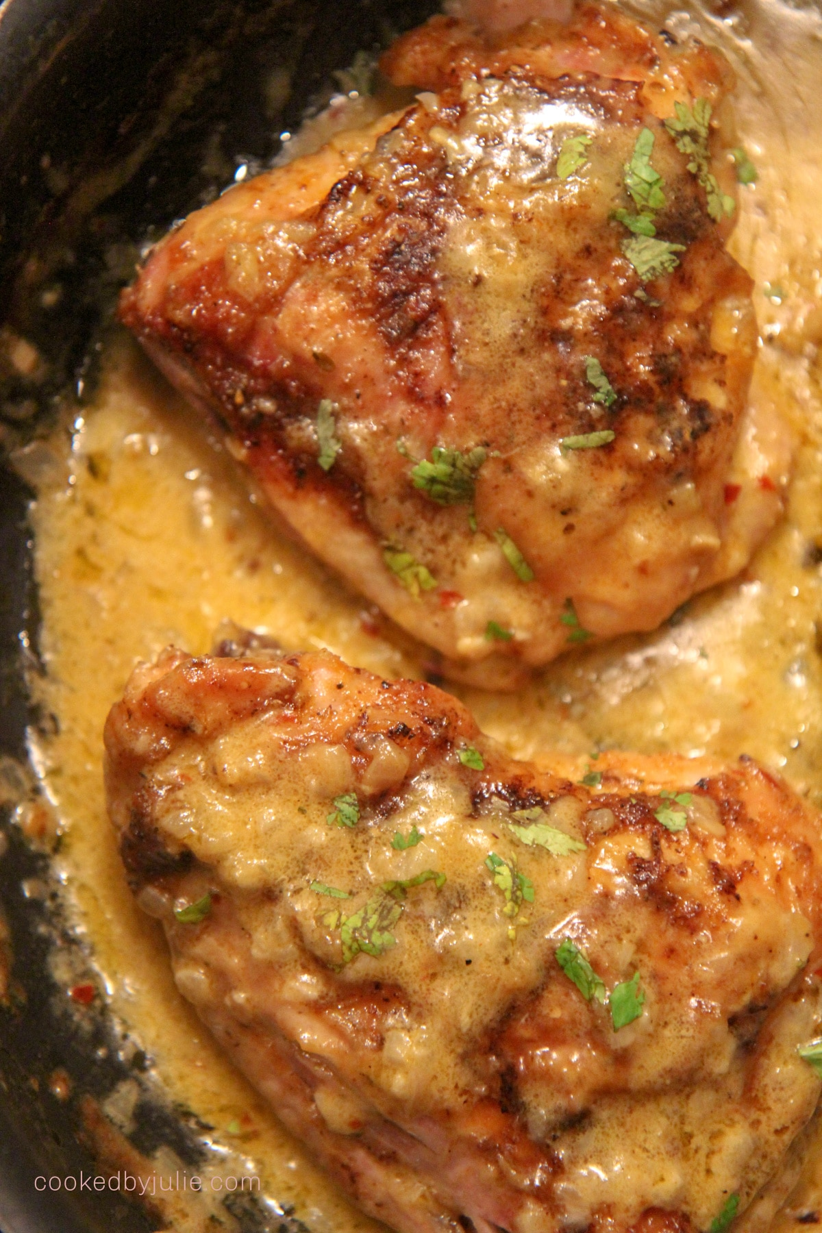 two chicken thighs with cream in a black skillet