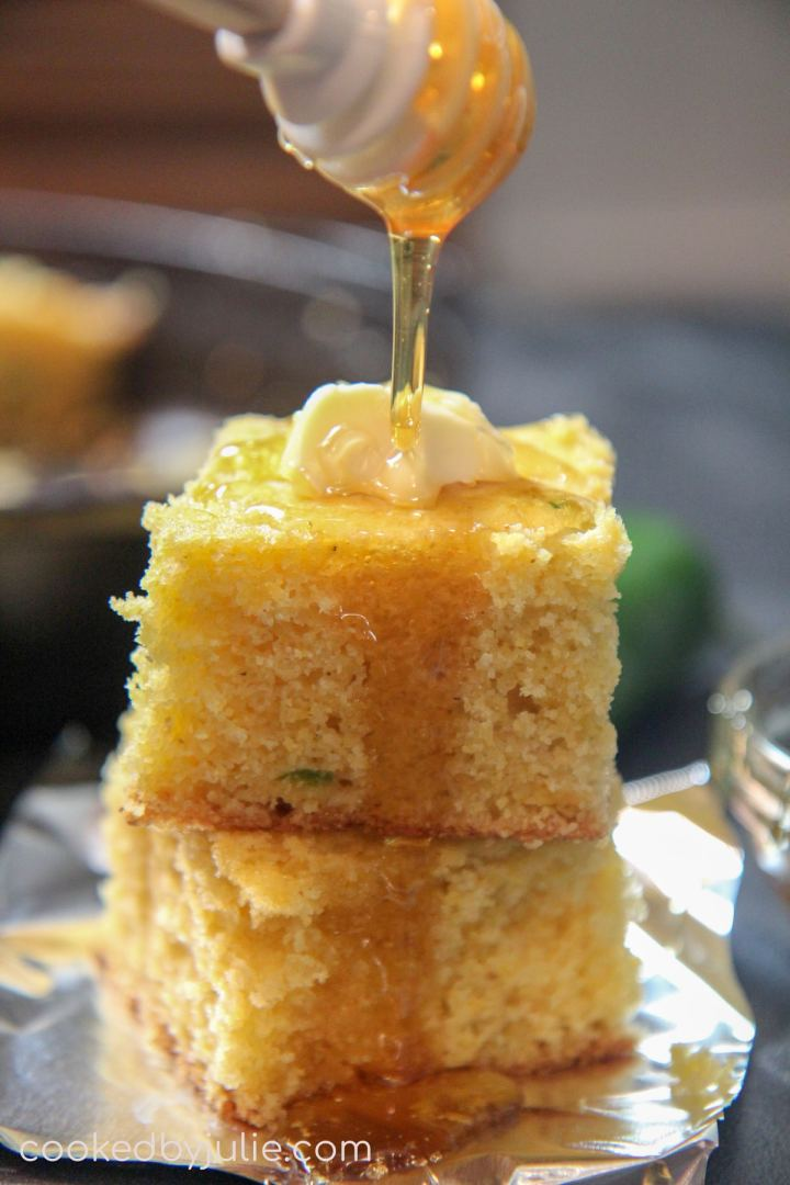 a honey comb pouring maple syrup over two slices of cornbread.