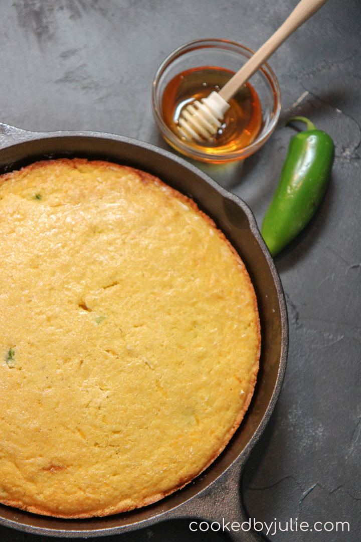 a cast iron skillet with cornbread and a honey comb and small bowl with syrup. A jalapeno pepper in the background.