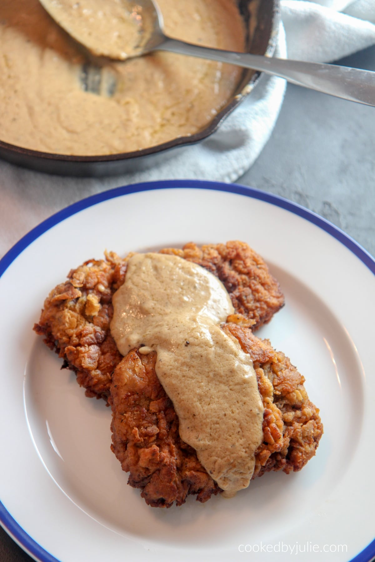 two chicken fried steak cutlets with gravy on top and an iron skillet with gravy and a spoon in the background.